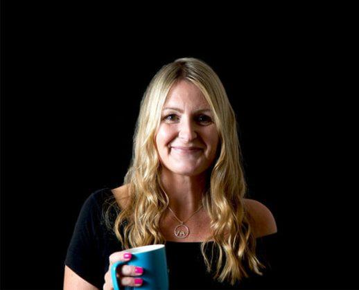 Blond-haired Lizzie Chantree smiles with blue coffee mug in right hand