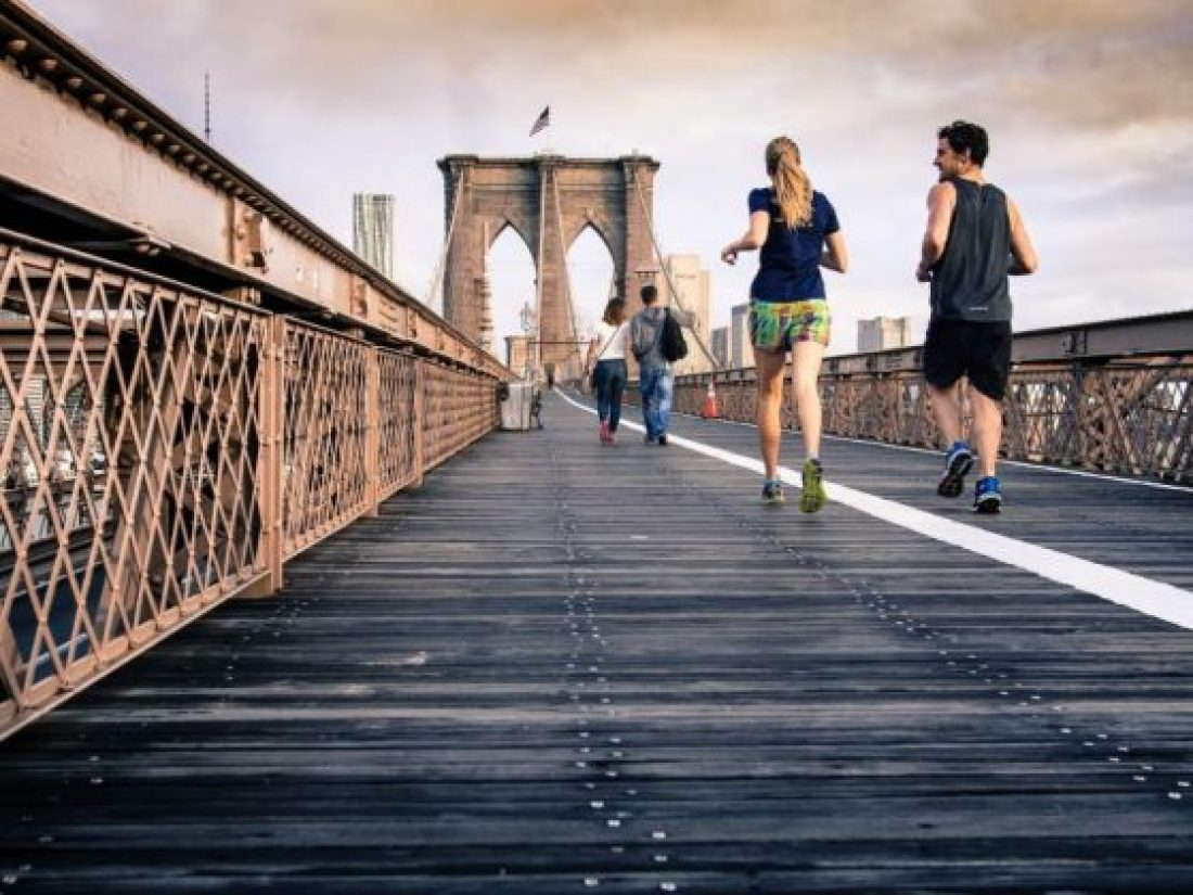 A woman and man in shorts and t-shirts run across a bridge