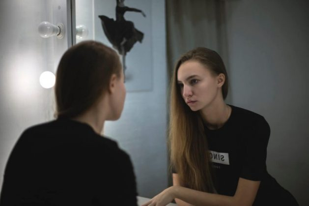 Young woman looks critically into mirror at her facial skin, seeking tips for dry skin.