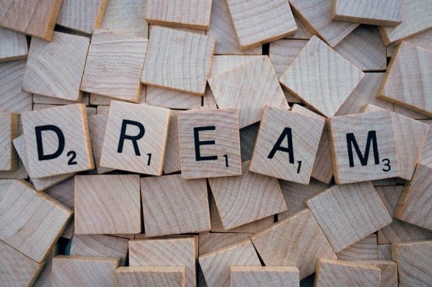 5 Scrabble tiles arranged to form the word Dream atop a bed of blank tiles