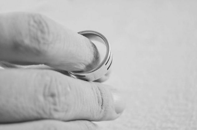 Woman plays with wedding ring b&w image while coping with divorce stress.