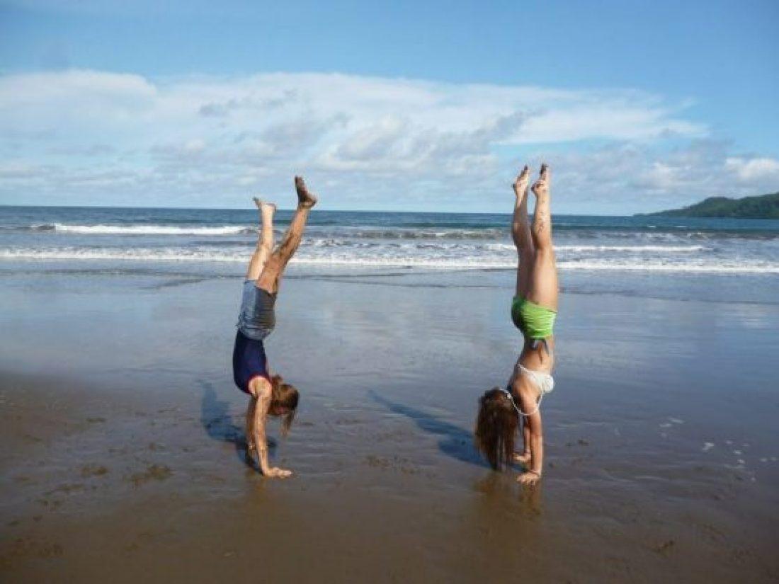 Deux femmes, faisant des roues de charrette sur une plage de sable, se deviennent en forme pour l'été