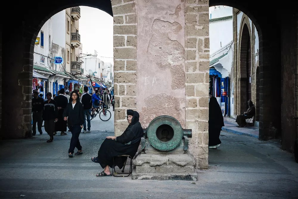 Old woman sitting at the gateway to the Medina in Essaouira, Morocco