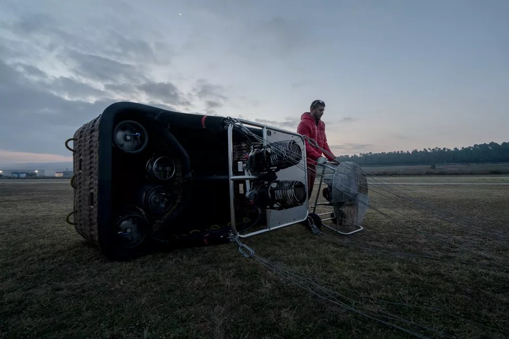 Pilot prepping hot air balloon at dawn