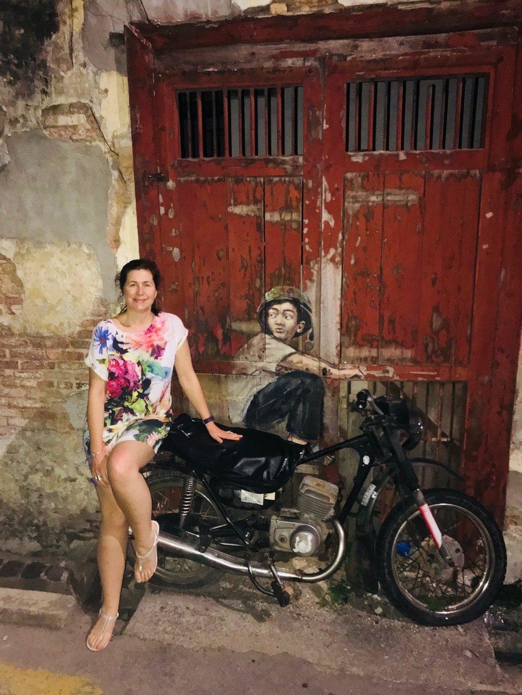 Angie next to boy on motorbike street art in Penang Malaysia