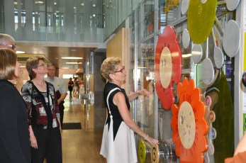 Premier Wynne tries out the Discovery Wall in the children's library at Central.