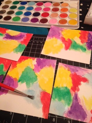 painting with rainbow color water colors filling all five tiny sheets of paper