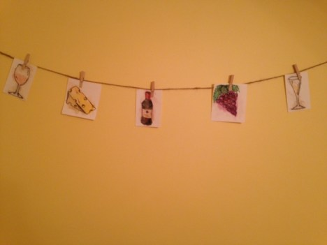 hanging watercolor pictures of wine glasses, cheese, wine bottle, and grapes