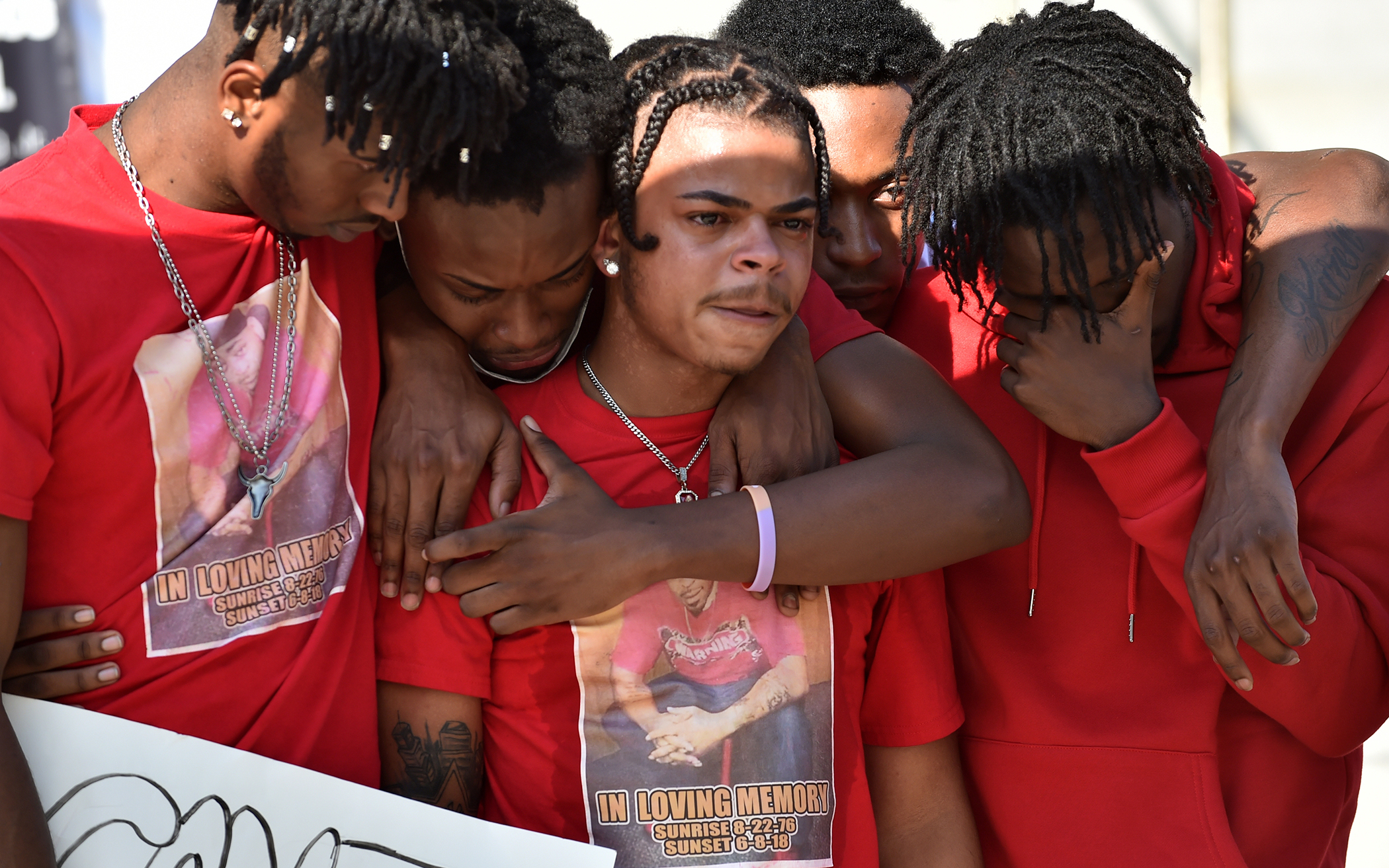 Five young men mourning and comforting each other at rally for the young man's father Shaheen Mackey who died after being detained by correction officers.