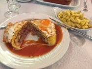 Francesinha - sandwich with smoked sausage, garlic beef, other meat (idk man), with melted cheese and fried egg, served in beer sauce. I ate half and tapped out.