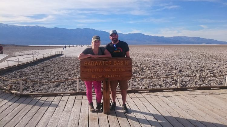 Couple at bad water basin sign death valley USA