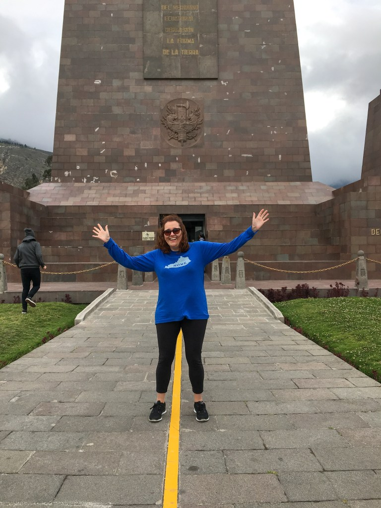 woman at the Equator with one foot in the southern hemisphere and another in the northern hemisphere