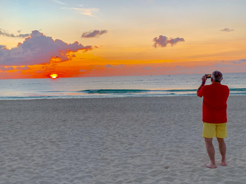 Man taking a picture of the sunrise on a beach in Mexico.  Packing list for Mexico.