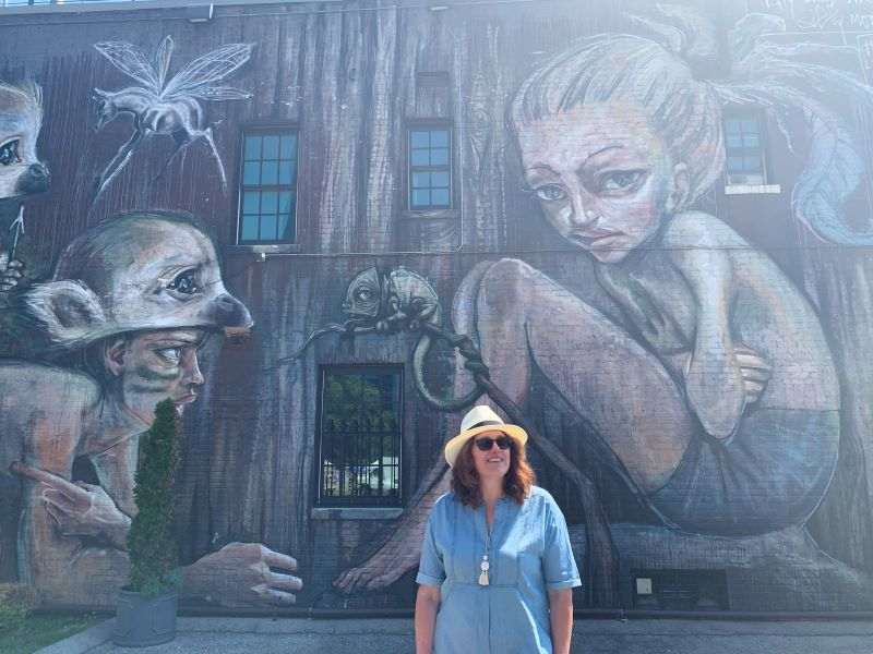 Woman standing in front of art mural on the side of a building in Lexington, Kentucky
