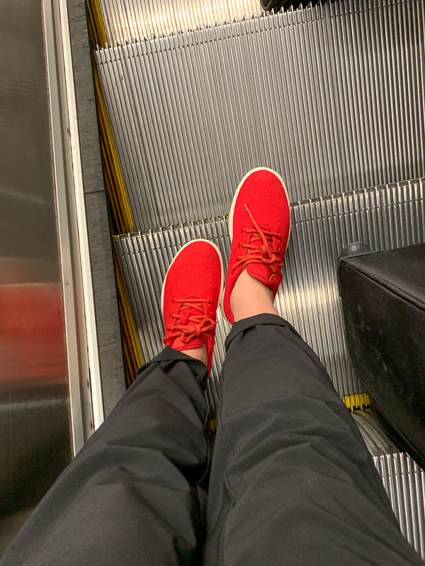 Pair of feet wearing red Allbirds shoes standing on an escalator. Eco-friendly gift-giving guide.