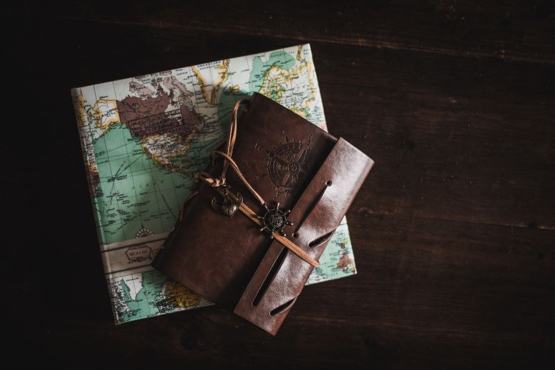 Map and brown leather journal on a wooden table. Easy travel journal ideas for keeping a journal when you travel.