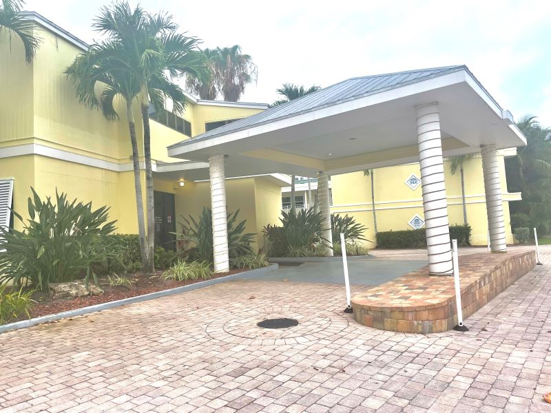 Paved brick entrance and a yellow hotel building. Neptune Resort in Fort Myers Beach, Florida
