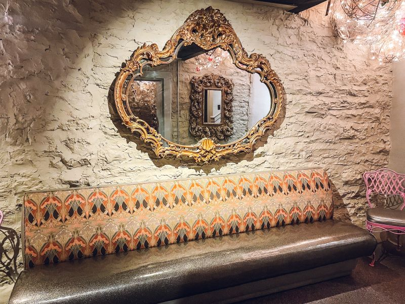 Long upholstered bench in front of a masonry wall with a large gilded, gold mirror hanging over it at Irish Acres Gallery, one of the most interesting antique shops in Kentucky.