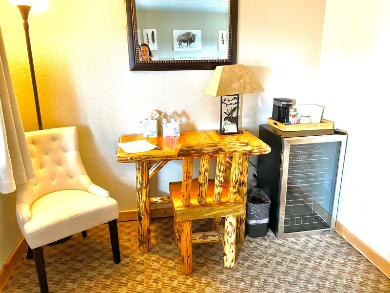 Wooden desk and chair, upholstered chair, and small refrigerator at best hotel West Yellowstone