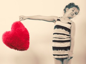 Little girl kid with red heart shape pillow.