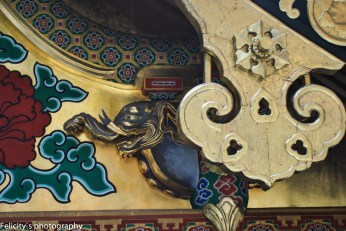 A cobalt elephant peaks out from gold gilt carvings atop the shrine roofs.