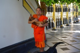 A buddhist monk carrying his puppy