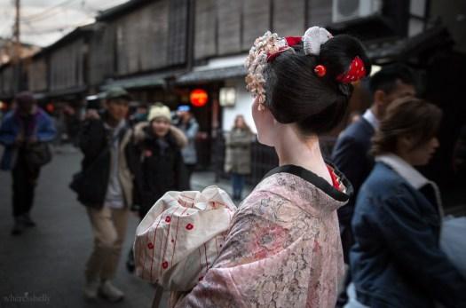 A maiko walks through Gion