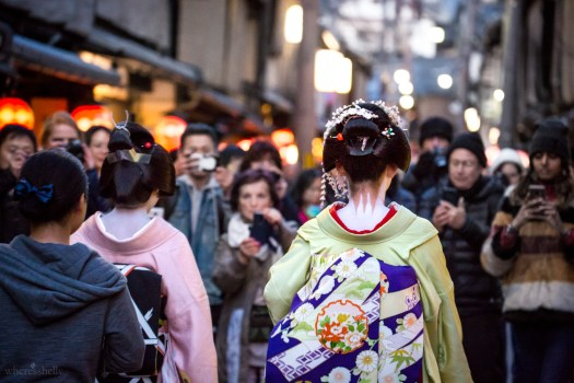 Geisha walk down a street surrounded by tourists with camera phones