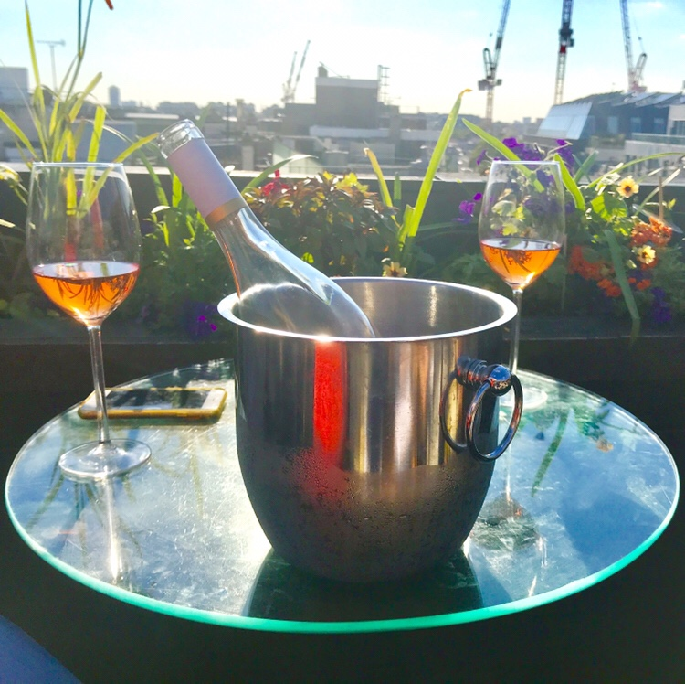 Aqua rooftop bar in Oxford Street, London with a bottle of rose wine in a bucket and glasses of wine