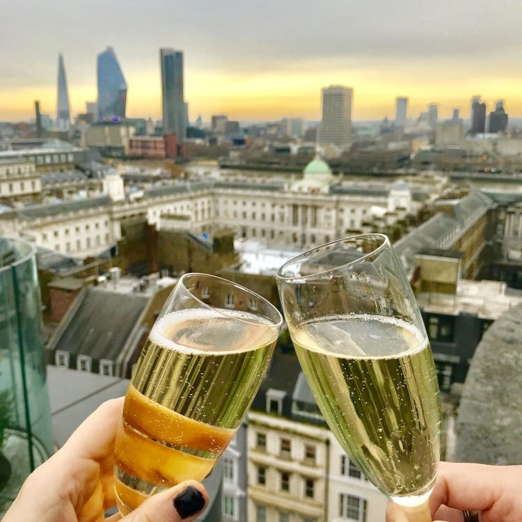 2 champagnes glasses together with somerset house in the background
