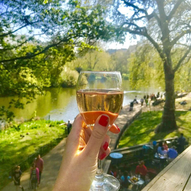 Glass of Rose being held overlooking St James Park