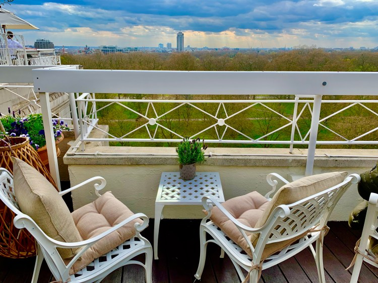 2 empty chairs sat overlooking Hyde park from a rooftop bar