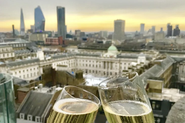 2 champagne glasses over Somerset house from radio rooftop