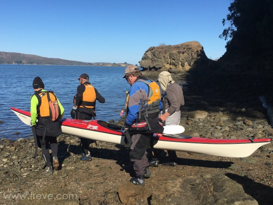 Moving a kayak loaded with gear. Four people with two webbing straps.