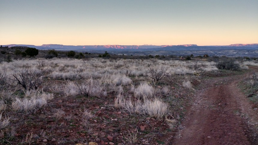 Sage brush with Camp Verde in the valley, the rocks of Sedona in the distance and the farthest mountains of Flagstaff.