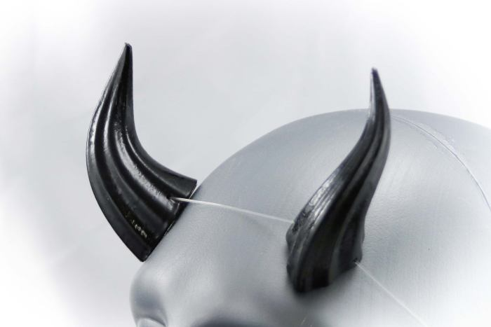 black, shiny, horns on a light grey model head