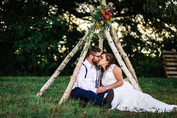 Bride Lace Bridal Gown With Buttons Groom Navy Pants Suspenders Cream Bow Tie Teepee Multicoloured Florals Pink Yellow Red Cushions Trees Grass Ethereal Boho Wedding Ideas http://perfectcapturephoto.com/
