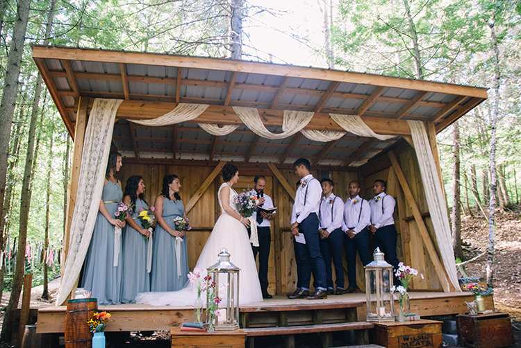 Outdoor Ceremony Bride Groom Bridesmaids Groomsmen Decorated Wooden Shelter Lace Silver Candle Lanterns Multicoloured Florals Vases Vintage Books Wooden Boxes Woodland Waterfall Mint Wedding Ontario http://www.laurenmccormickphotography.com/