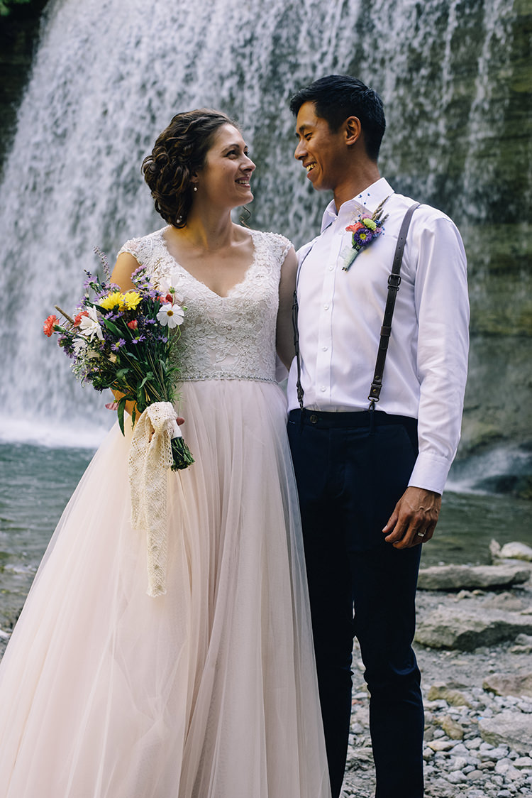 Bride Allure Champagne Lace Tulle Bridal Gown Multicoloured Floral Bouquet Lace Ribbon Groom White Shirt Brown Leather Suspenders Navy Pants Multicoloured Floral Buttonhole Woodland Waterfall Mint Wedding Ontario http://www.laurenmccormickphotography.com/