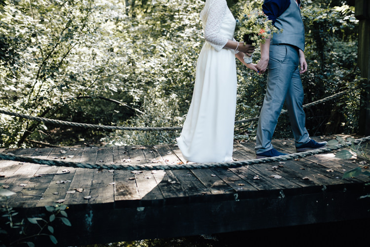 Outdoor First Look Bride Handmade Lace Floral Belt Bridal Gown Bouquet Orange Carnations Thistle Gypsophila Groom Grey Vest Pants Navy Blue Shirt Buttonhole Orange Florals Succulent Adventure Inspired Woodland Wedding North Carolina http://www.amandasuttonphotography.com/