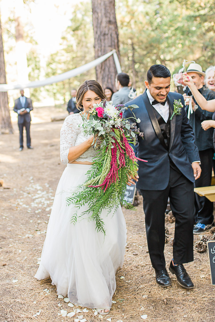 Outdoor Ceremony Bride Watters Separates Lace Top Tulle Skirt Cascading Multicoloured Bouquet Groom Dark Blue Jacket Black Satin Lapel Black Pants Vest Bowtie Floral Buttonhole Guests DIY Whimsical Camp Wedding California http://www.landbphotography.org/