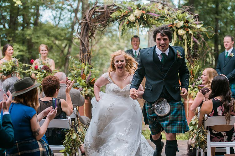 Bride Groom Running out of Ceremony Vows Tartan Kilt Dress Cap Sleeve Lace Curls Archway Branches Whimsical Woods Wedding Barn Ohio http://www.connectionphotoblog.com/