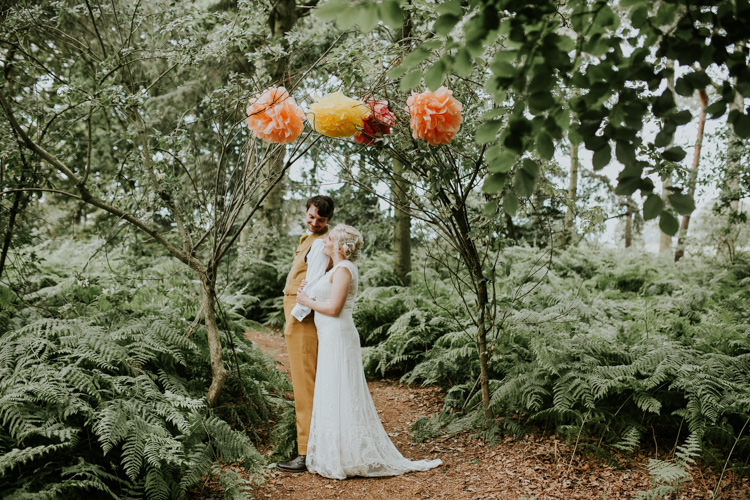 Field Outdoor Tipi Hippie Bride Groom Paper Pompoms Flower Arch | Happy Outdoor Forest Mustard Yellow Wedding http://suzi-photography.com/