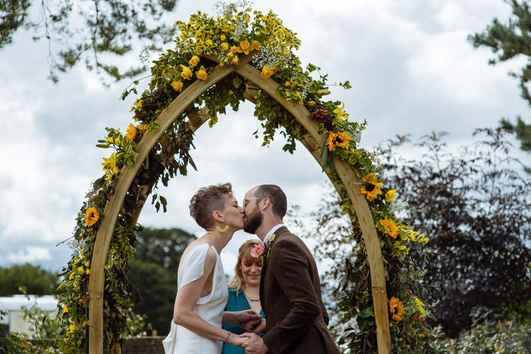DIY Ceremony Bride Groom Kiss Yellow Wildflower Floral Arch Seasonal Alternative Hippy Farm Field Garden Wedding | Homegrown Community Eclectic Rural Yorkshire Wedding https://toastofleeds.co.uk/