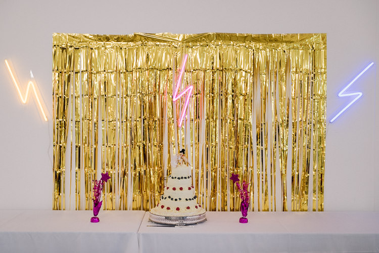 Cake Table Backdrop Gold Curtain Streamers Lightning Bolt Neon Lights Colourful Indie London City Wedding Clissold House West Reservoir Centre https://www.murrayclarke.co.uk/