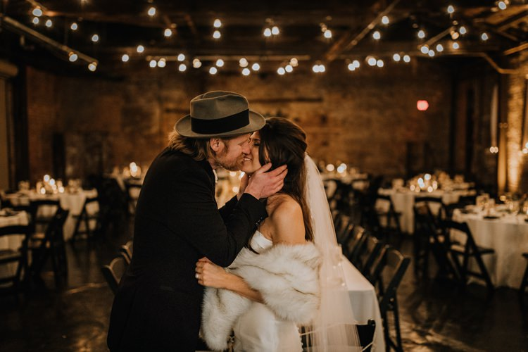 Warehouse Modern Refined Rustic Chic Festoon Lighting Bride Groom Kiss | Boho Industrial Winter Wedding Lunalee Photography