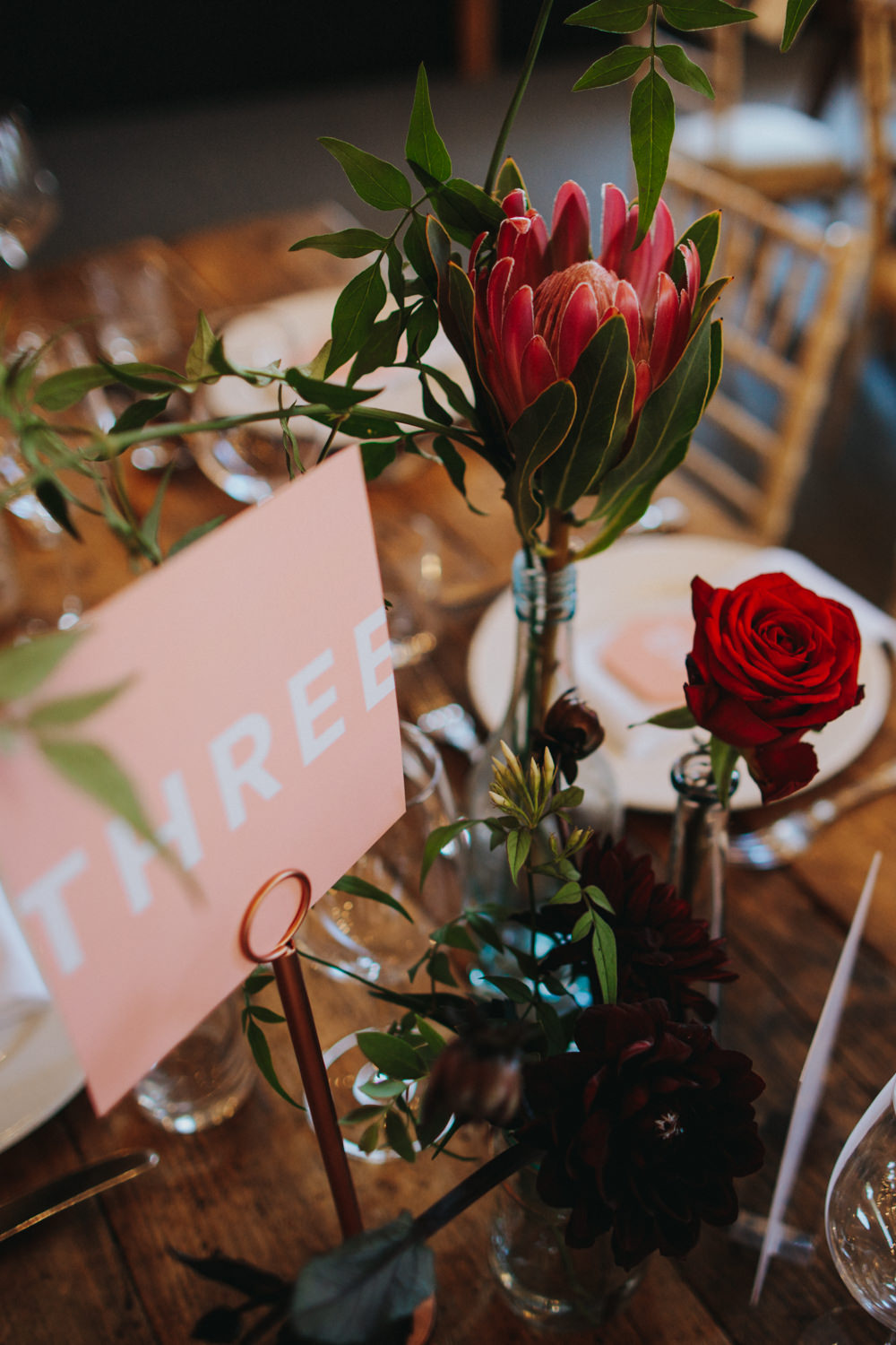 Protea Rose Bottle Copper Red Flowers Pink Graphic Table Names Numbers Godwick Great Barn Wedding Joshua Patrick Photography
