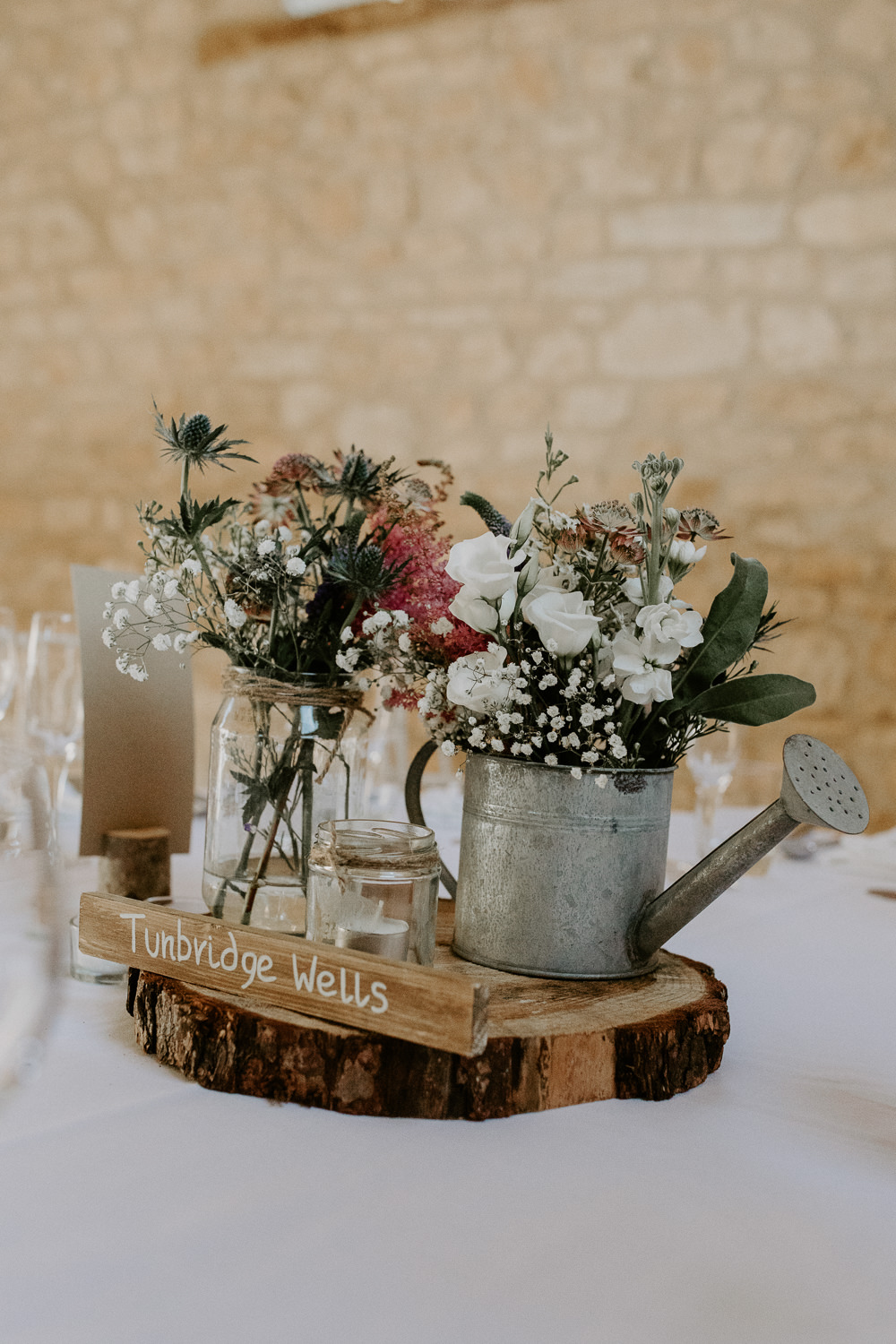 Flowers Watering Can Pink Grenery Thisle Astilbe Centerepice Log Rustic Table Barn Upcote Wedding Siobhan Beales Photography