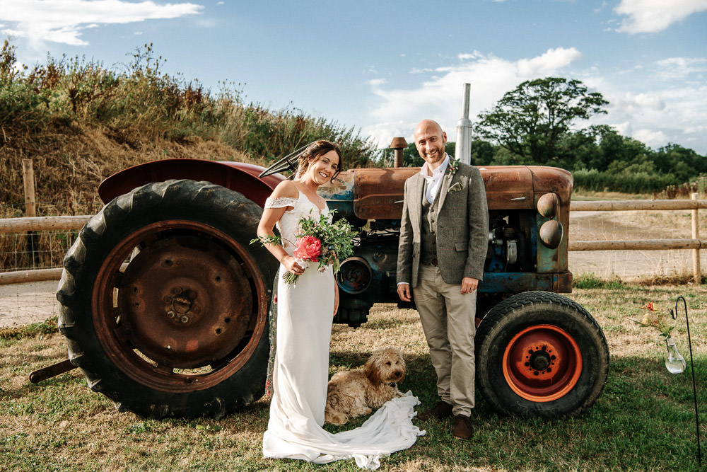 Bride Bridal Dress Gown Lace Detail Drop Cold Shoulder Ribbon Bow Sleeveless Tweed Suit Waistcoat Groom Floral Veil Stanford Farm Wedding Andy Griffiths Photography