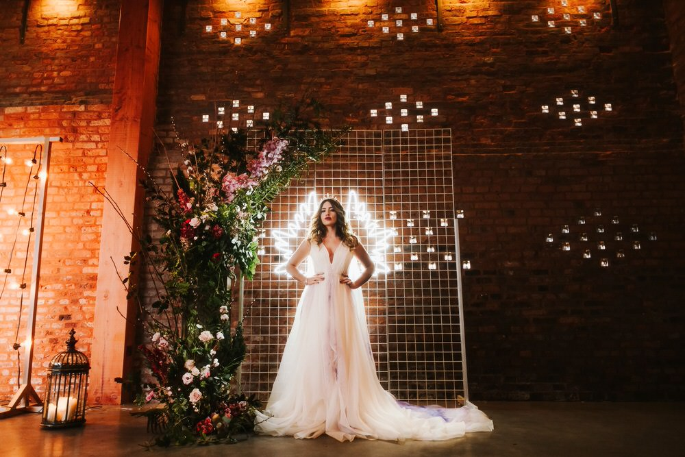 Flower Installation Backdrop Neon Sign Greenery Foliage Metal Bride Bridal Dress Gown Train Tulle Romantic Wedding Ideas Neon Lighting Kate McCarthy Photography